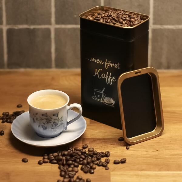 Kaffeburk i svartlackad metall med graverad text: ...men först kaffe.