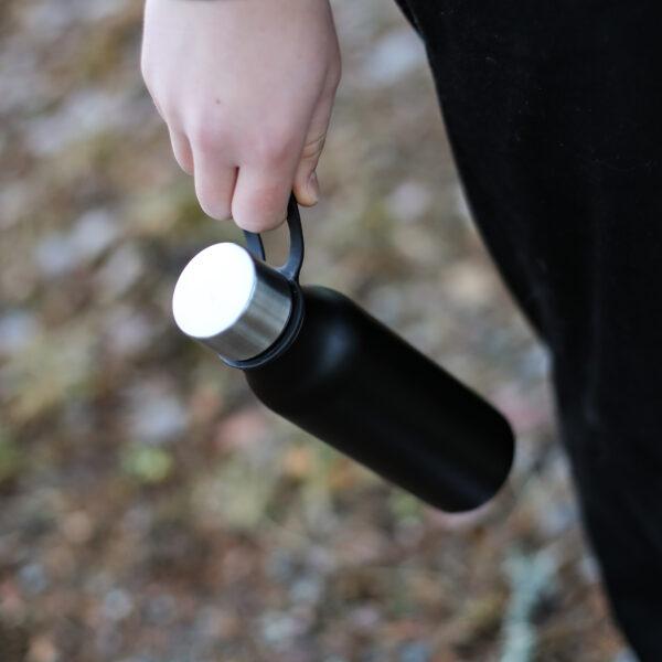 Hand håller i vatttenflaska i metall