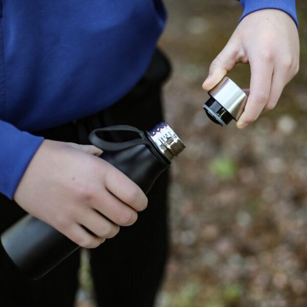 Vattenflaska i metall, Märke: Lean, 450 ml. Hand som öppnar flaskan