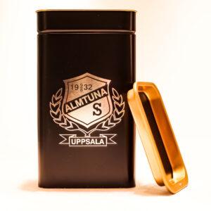 Almtunas emblem graverat på kaffeburk i metall