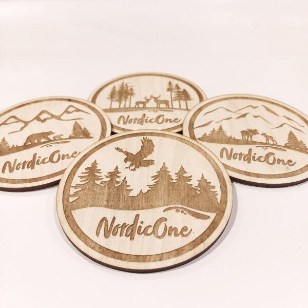 Glasunderlägg i trä med NordicOne-motiv. Örnen, Älgar, Björnar, Renar