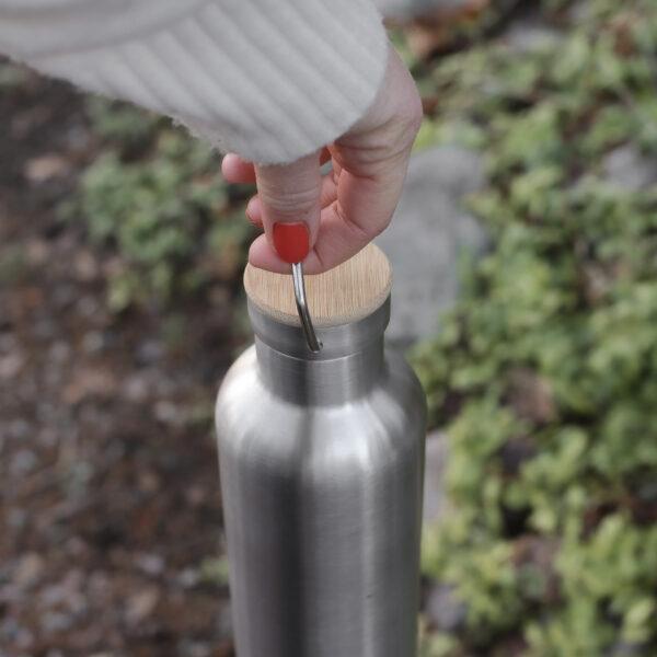 Hand håller i Miles termosflaska i metall, 1 liter, rostfri